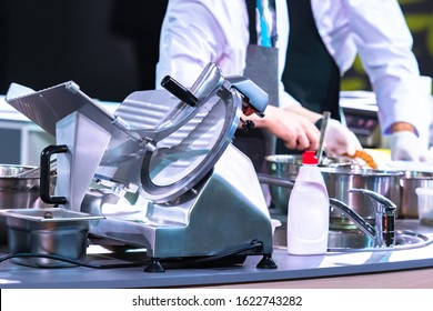 Slicer in the restaurant kitchen. Concept - Slicer washed with detergent. Detergent for kitchen appliances. Professional semi-automatic slicer. Machine with a cutting disc. Grocery Store Equipment.