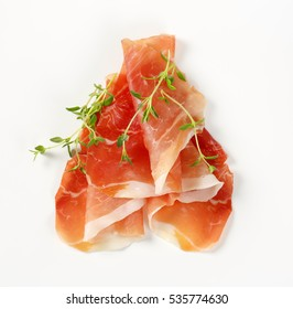 slices of air dried ham with thyme on white background