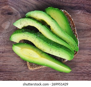 Slices of avocado on a rye bread on a wooden board