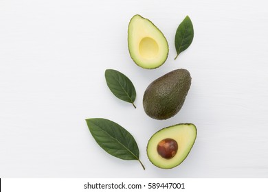 Slices of avocado on white background. Whole and half with leaves. Design element for product label.