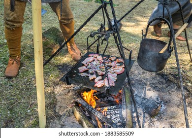 Slices of bacon and chopped onion on a campfire. Homemade food at historical reenactment of Slavic or Vikings lifestyle from around 11th century, Cedynia, Poland