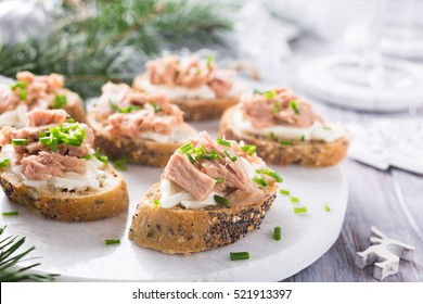 Slices of baguette with fresh tuna, cream cheese and chopped onion chives on marble board. Christmas themed dinner table.