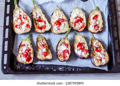 Slices of baked aubergines with tomatoes on a baking tray