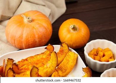 Slices of baked pumpkin in white ceramic bowl on brown wooden table, selective focus. Vegetable dish, vegan diet, healthy food