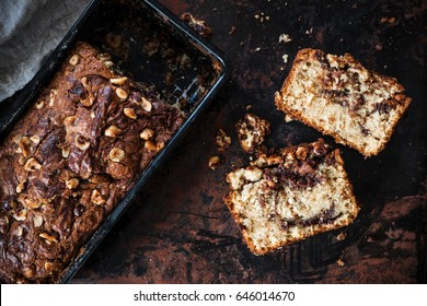 Slices of banana bread with hazelnut and chocolate, loaf cake from above. Dark food photography.