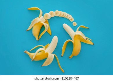 slices of banana on bright blue paper, trendy fruit modern flat lay. juicy  vitamin abstract background. time to eat and diet concept. pop art style. open and sliced banana pattern
