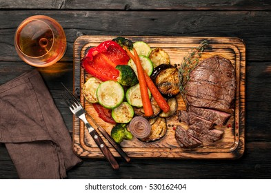 Slices of beef steak with grilled vegetables on cutting board on dark wooden table with a glass of brandy or whiskey