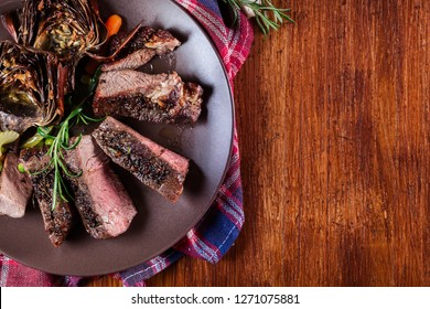 Slices of beef steak served with baked artichoke on a plate. Top view