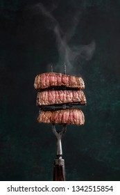 Slices of beef steak with steam on vintage fork on dark background