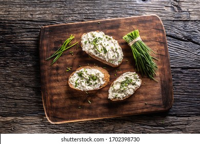 Slices of bread with a cottage cheese spread, freshly cut chives, and a bunch of chive aside placed on a dark brown cutting board and vintage background.