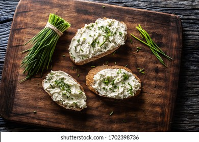 Slices of bread with a cottage cheese spread, freshly cut chives, and a bunch of chive aside placed on a dark brown cutting board.