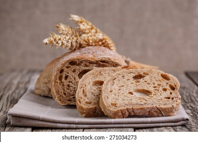 Slices of bread with rye on a wooden background.