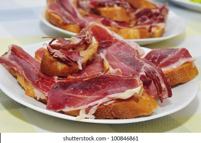 slices of bread with spanish serrano ham served as tapas
