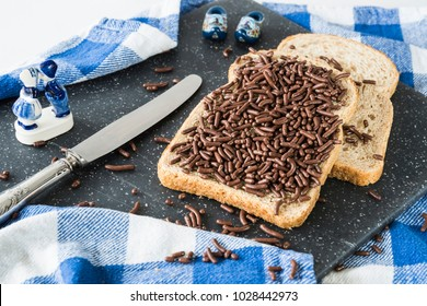 slices of brown bread, wheat, whole grain with typical Dutch hagelslag, chocolate hail. Silver knife, Dutch Delfts blue souvenir, wooden shoe