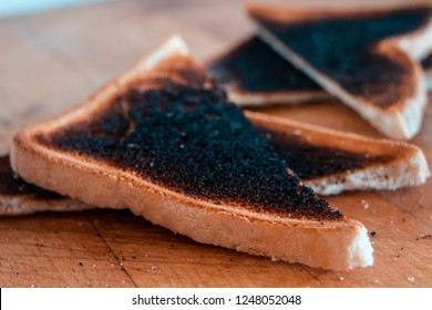Slices of burnt toast of white bread on wooden board