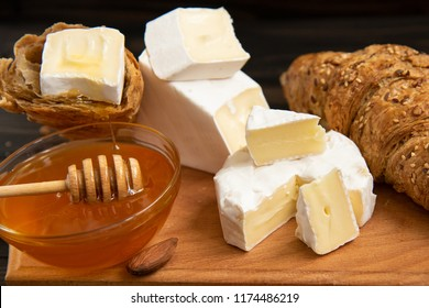 slices of cheese brie or camembert with croissants, honey and nuts on board for cutting, on dark wooden background