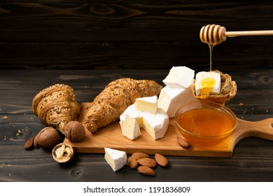 slices of cheese brie or camembert with croissants, honey and nuts on board for cutting, on dark wooden background. copy text.