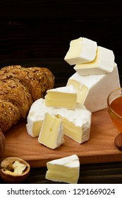 slices of cheese brie or camembert with croissants, honey and nuts on board for cutting, on dark wooden background.