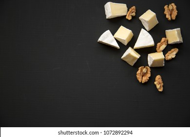 Slices of cheese camembert or brie  with walnuts. Milk production. Top view. Flat lay. From above. Copy space.