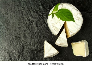 Slices of cheese camembert on a slate board. Healthy cheese. Dairy products. Cheese with noble mold.