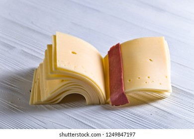 Slices of cheese folded like a book on a white wooden table .