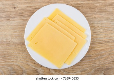 Slices of cheese in white plate on wooden table. Top view