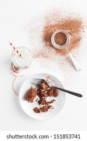 Slices of chocolate brownie sprinkled with cocoa powder served on white plate.Served with cocoa powder and sifter,with glass of milk with red white stripe straw.Taken on white background, from above.