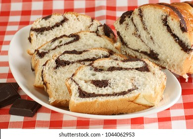 slices of chocolate filled briche on a red gingham cloth