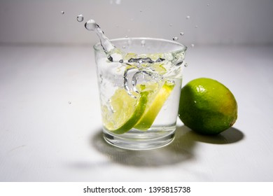 """Slices of citrus, green fruit lyme """"Citrus aurantiifolia"""" fall into clear water, alcoholic beverage. Transparent glass, spray, water drops. White background, slow motion."""