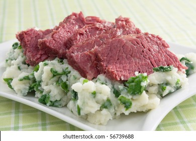 Slices of corned beef on top of colcannon (mashed potatoes with kale).
