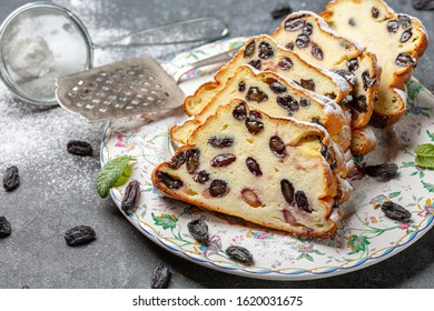 Slices of cottage cheese casserole with vanilla, semolina and raisins are served on a ceramic dish and a strainer with powdered sugar for sprinkling on a dark background, selective focus.