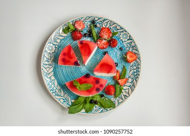 Slices of cottage cheese pie with strawberries, mint and frozen blueberries on a plate