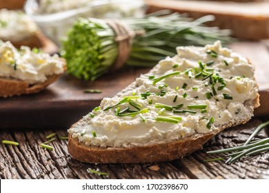 Slices of crusty bread with a cream cheese spread and freshly cut chives on a vintage wooden cutting board.