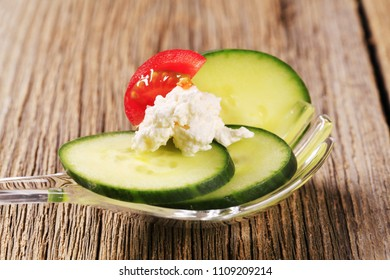 Slices of cucumber and cheese on a salad spoon