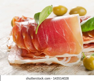 Slices of cured ham on  wooden table . Selective focus