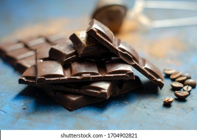 slices of dark chocolate with cocoa on a dark blue background