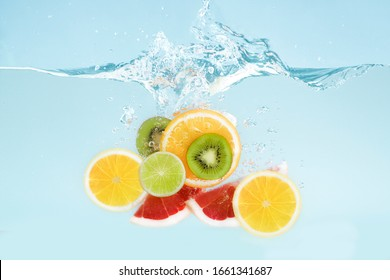 Slices of different tropical fruits falling into transparent water with splashes on blue background