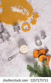 Slices of dried orange and a branch of pine Christmas cookies cutters on marble surface.