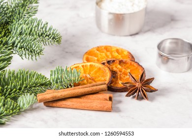 Slices of dried orange and a branch of pine on marble surface.