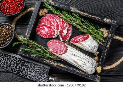 Slices of dry cured salchichon salami in a wooden tray. Black wooden background. Top view.