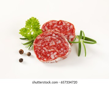 Slices of dry cured sausage with herbs and peppercorns on white background