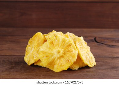 Slices of dry pineapple on a wooden background.