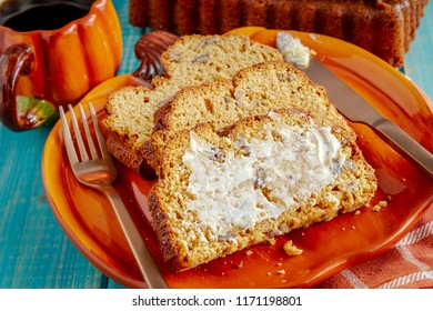 Slices of fresh baked pumpkin bread with butter on pumpkin shaped plate with cup of coffee