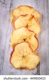 Slices of fresh dried apple lying on old rustic wooden background