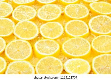 A slices of fresh juicy yellow lemons.  Texture background, pattern.