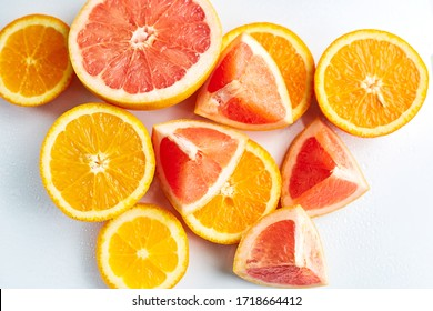 Slices of fresh orange and grapefruit on white background top view. Citrus Juice Concept, Vitamin C, Fruits. Creative summer background