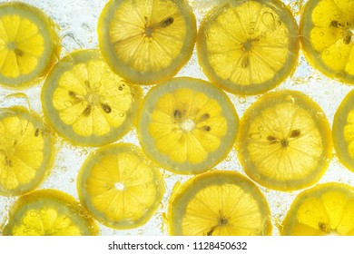 Slices of fresh, organic lemon fruit in water with bubbles.
