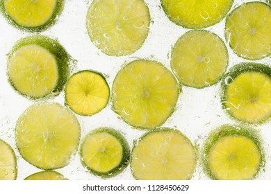Slices of fresh, organic lime fruit in water with bubbles