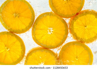 Slices of fresh, organic orange fruit in water with bubbles.