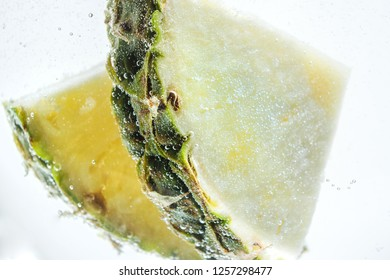 Slices of fresh pineapple in clear water. Close-up photo.